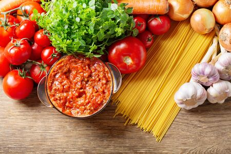 sauce bolognese with fresh vegetables for cooking on wooden table, top view