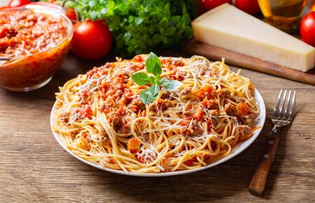 plate of pasta bolognese on wooden table