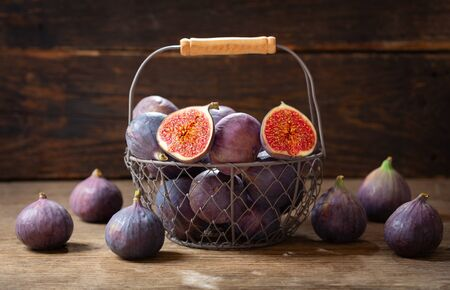 fresh figs fruit in a basket on a wooden table