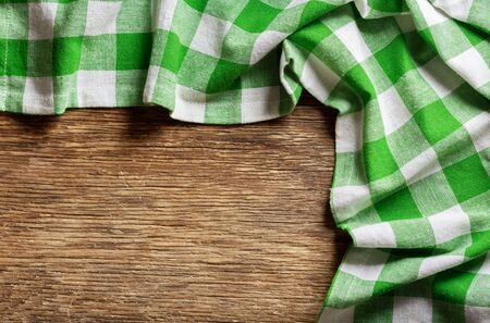green checkered tablecloth on wooden table, top view Reklamní fotografie