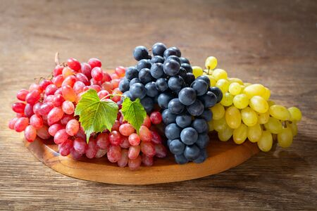 mix of fresh ripe grapes with leaves on a wooden board Reklamní fotografie