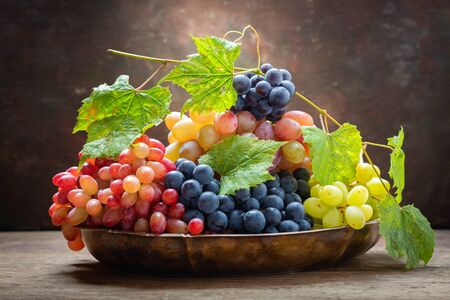 mix of fresh ripe grapes with leaves in a bowl on a wooden table Reklamní fotografie