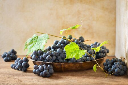 fresh ripe grapes with leaves in a bowl on a wooden table Reklamní fotografie