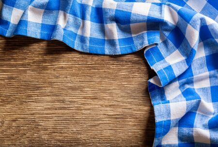blue checkered tablecloth on wooden table, top view Reklamní fotografie