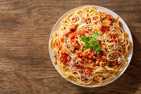 plate of pasta bolognese on wooden background, top view
