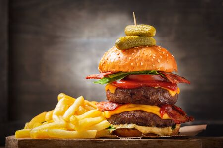 big double hamburger with cheese, bacon, salad, vegetables and french fries on wooden  board Reklamní fotografie