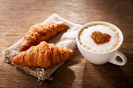 Valentinstag. Tasse Cappuccino-Kaffee mit gezogenem Herzen und frischen Croissants auf Holztisch, Ansicht von oben