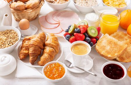 Breakfast with croissants, coffee, juice, meat, jam, cereals and fresh fruits on a wooden table