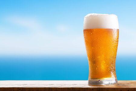 bicchiere di birra freddo su un tavolo di legno sullo sfondo del mare