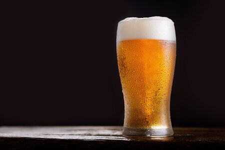cold glass of beer on dark background