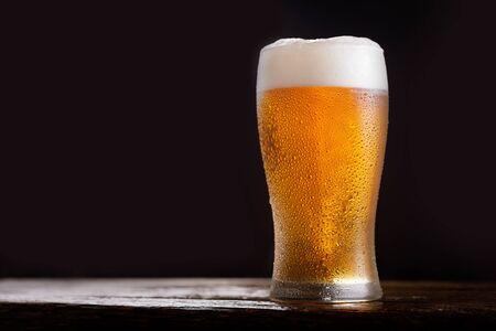 Vaso de cerveza fría sobre fondo oscuro