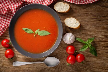 A bowl of tomato soup with basil on wooden table, top view