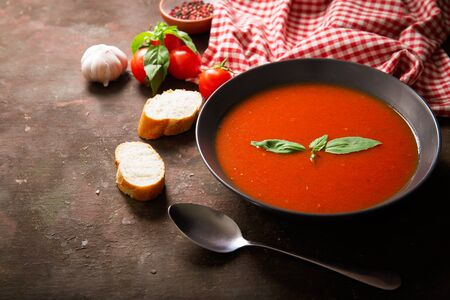 A bowl of tomato soup with basil and ingredients for cooking