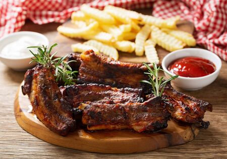Grilled pork ribs with rosemary and french fries on a wooden table