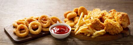 fast food meals : onion rings, french fries, chicken nuggets and fried chicken on wooden table