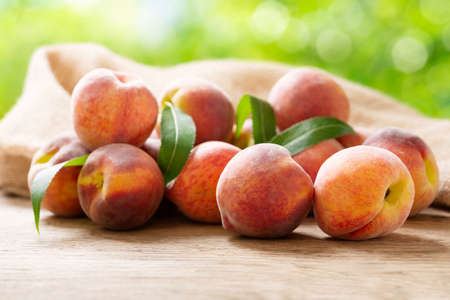 fresh ripe peaches with leaves on a wooden table in a garden