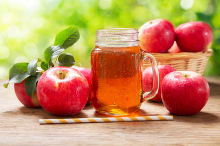 glass jar of apple juice with fresh fruits on a wooden table