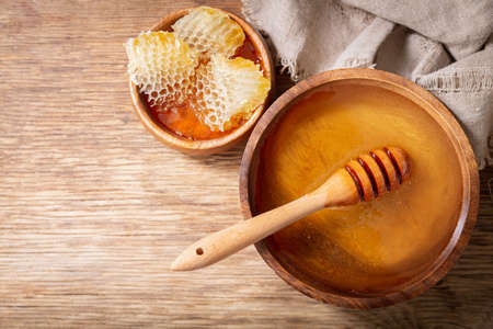 bowl of honey and honeycombs on a wooden table, top view