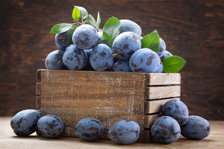 fresh ripe plums in a box on a wooden background