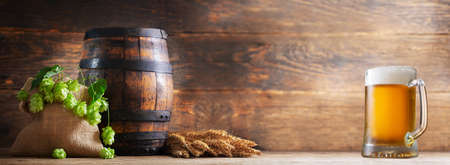mug of beer, wheat ears, hops and barrel on a wooden background