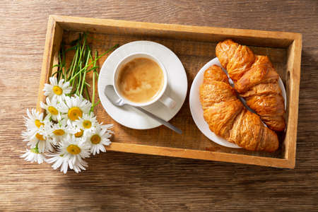cup of coffee, croissants and daisy flowers on a wooden tray, top view 版權商用圖片