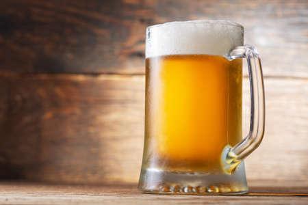 cold mug of beer on a wooden background