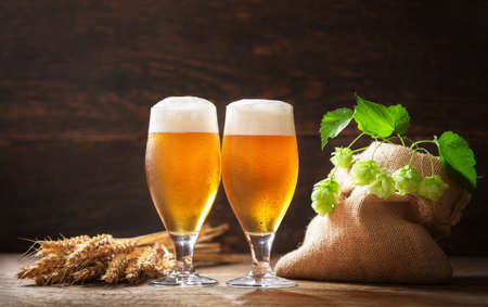 glasses of beer, wheat ears, hops and barrel on a wooden background 版權商用圖片