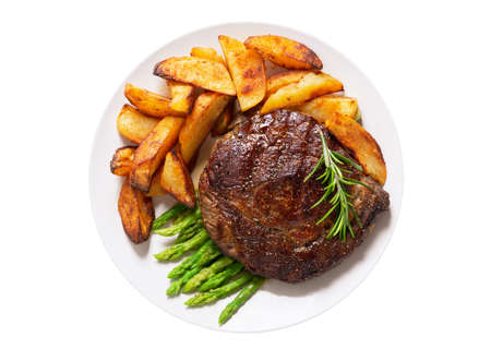 plate of grilled steak with rosemary, asparagus and potato isolated on a white background, top view