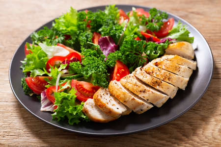 plate of chicken salad with vegetables on wooden table