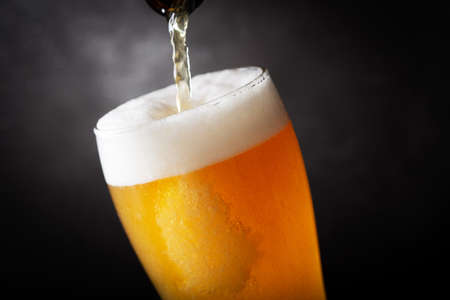 beer pouring into glass on a dark background