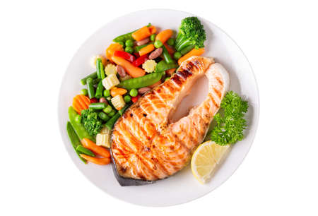 plate of grilled salmon steak with vegetables isolated on a white background, top view