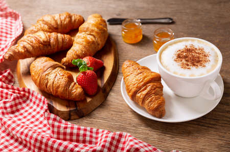 cup of cappuccino coffee, jam, strawberries and croissants on a wooden table 版權商用圖片