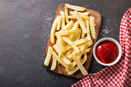 French fries with ketchup on dark table, top view 版權商用圖片