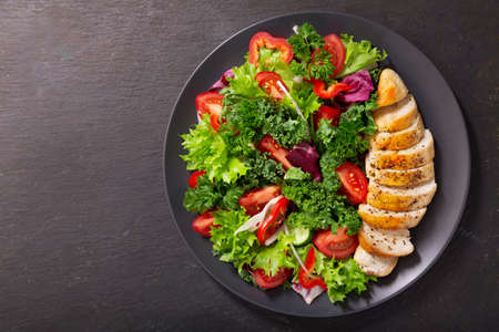 plate of chicken salad with vegetables on dark background, top view