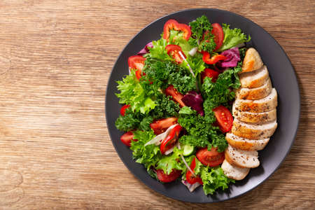 plate of chicken salad with vegetables on wooden background, top view 版權商用圖片