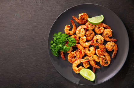 plate of grilled shrimps with lime on dark background, top view