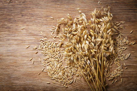 ripe ears of oat and grains on wooden background, top view