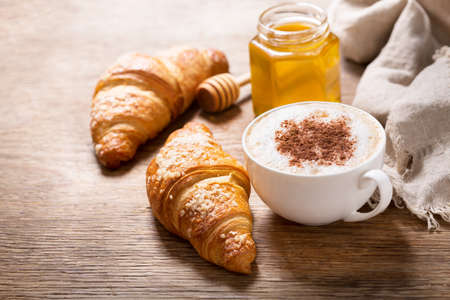 cup of cappuccino coffee and croissants on a wooden table 版權商用圖片