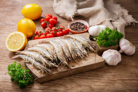 fresh shrimps with ingredients for cooking on a wooden table 版權商用圖片