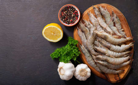 fresh shrimps with ingredients for cooking on a wooden board, top view
