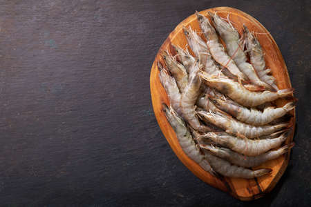 fresh shrimps on a wooden board, top view