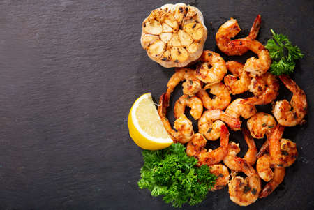 grilled shrimps with lemon and parsley on dark background, top view