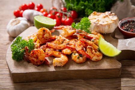 grilled shrimps with lime and parsley on a wooden board