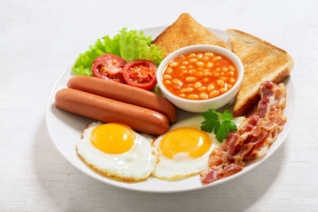 plate of fried eggs with bacon, beans, sausages, toasts and tomatoes on a wooden table