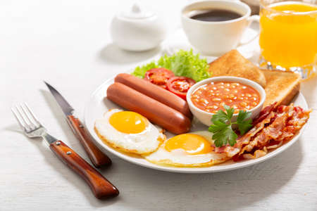 breakfast with plate of fried eggs, bacon, beans, sausages, toasts and tomatoes on a wooden table 版權商用圖片