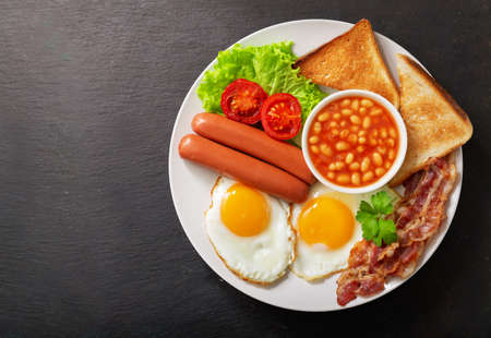 plate of fried eggs with bacon, beans, sausages, toasts and tomatoes on a dark background, top view
