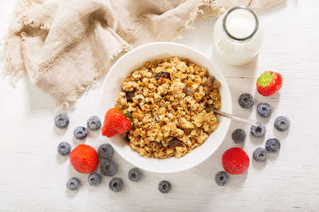 breakfast with bowl of granola, fresh berries and bottle of milk on a wooden table, top view 版權商用圖片