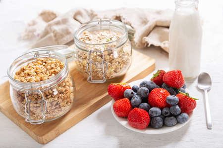 breakfast with granola, fresh berries and bottle of milk on a wooden table