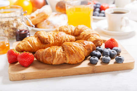 Breakfast with croissants, coffee, juice, jam, cereals and fresh fruits on a wooden table