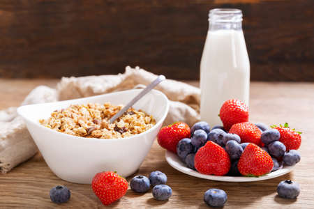 breakfast with bowl of granola, fresh berries and bottle of milk on a wooden table